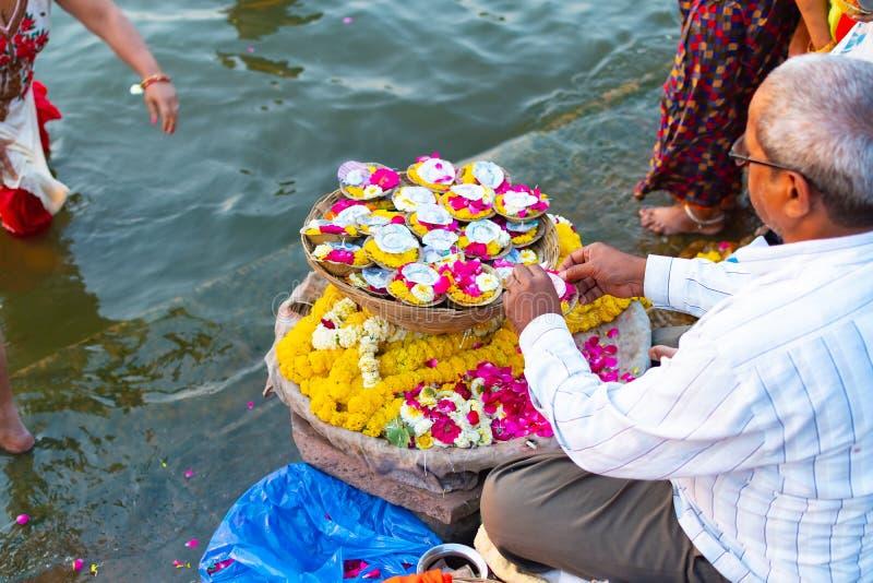 Varanasi, Índia, o 27 de março de 2019 - homem indiano que vende artigos das flores do pooja para o oferecimento fotos de stock