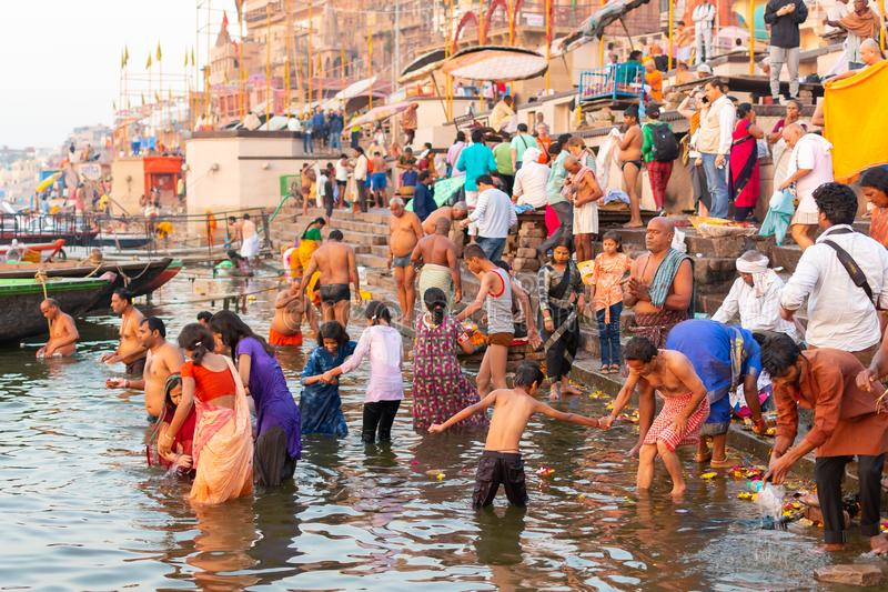Varanasi, Índia, o 27 de março de 2019 - mostrando a roupa tradicional colorida e o ritual religioso hindu do banho no fotografia de stock