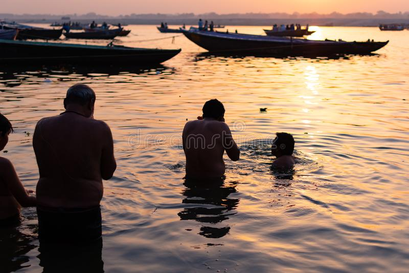 Varanasi At At the first morning Hindu devotee taking bath at holy ghats of Varanasi, India stock images