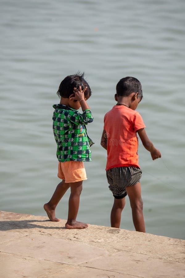 Varanasi, India, 15 de noviembre, 2019/ Life on the Ganges: pobres niños indios de castas bajas jugando en los pasos que llevan a fotos de archivo libres de regalías