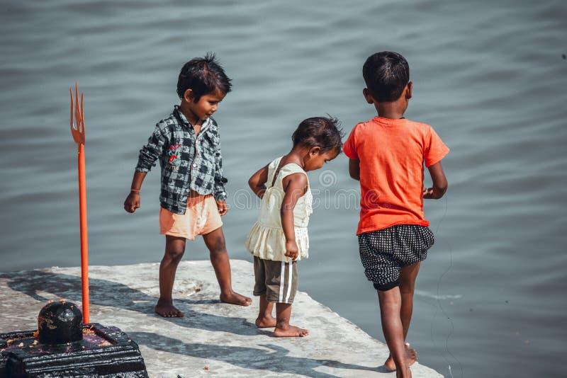 Varanasi, India, 15 de noviembre, 2019/ Life on the Ganges: pobres niños indios de castas bajas jugando en los pasos que llevan a imagenes de archivo