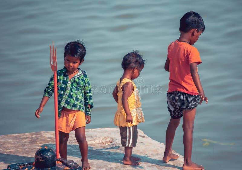 Varanasi, India, 15 de noviembre, 2019/ Life on the Ganges: pobres niños indios de castas bajas jugando en los pasos que llevan a fotografía de archivo