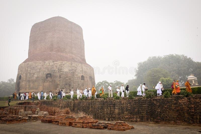 VARANASI INDIA, GRUDZIEŃ, - 2, 2016: Mnisi buddyjscy i turyści przychodzący odwiedzać i ono modlić się w mglistym ranku przy Dham fotografia stock
