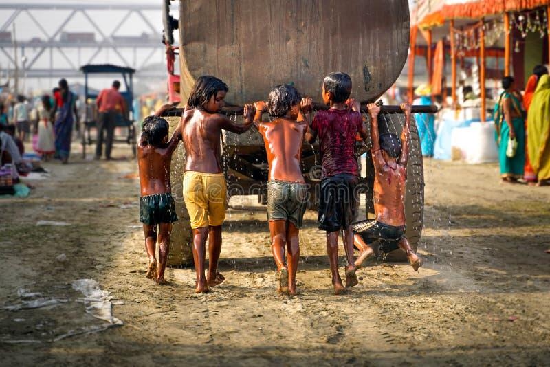 Varanasi/India-09 11 2018: indiska ungar som spelar med vattenbehållaren royaltyfri foto