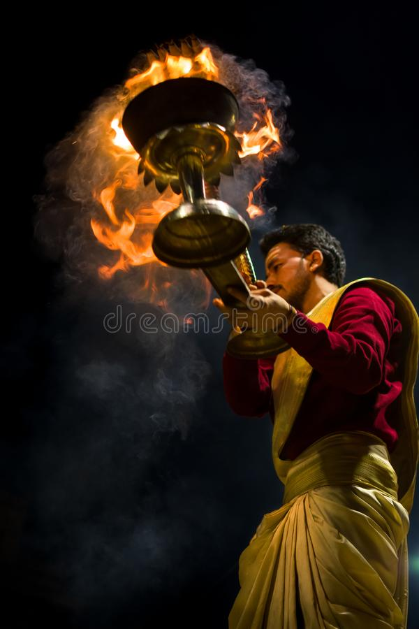 A priest holding a fire stand stock photography