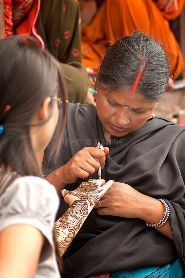 Varanasi, India - Juli 24, 2011: Hennatatoegering op hand door make-upkunstenaar stock foto