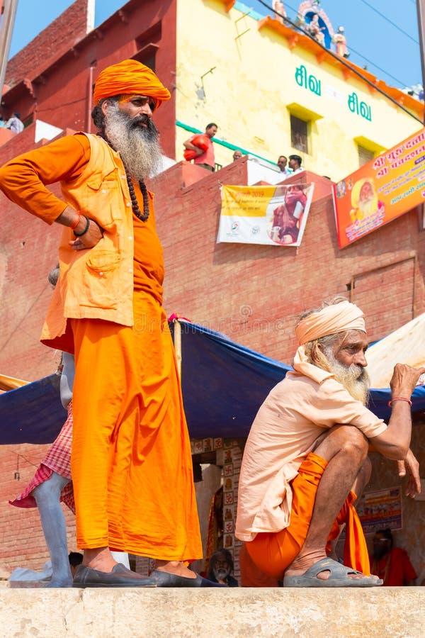 VARANASI, INDIA, MĄCI 10 2019, Dwa Niezidentyfikowanych Hinduskich sadhu świętego mężczyzny -, stoi na ghat blisko Ganges rzeki w fotografia royalty free