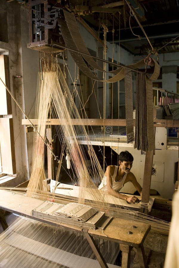 VARANASI, INDIA - A man makes a sari cloth. VARANASI, INDIA - DECEMBER 9: A unidentified Indian man makes a traditional sari cloth, hand loom on old fabric stock photo