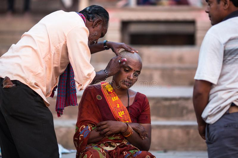 Hairdresser cuts hair of the pilgrim. VARANASI, INDIA - MAR 23, 2018: Hairdresser cuts hair of the pilgrim. A haircut in Varanasi is considered to be a kind of stock image