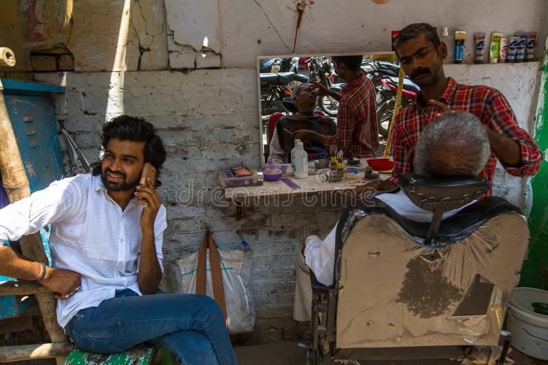 Hairdresser cuts hair of the pilgrim. VARANASI, INDIA - MAR 14, 2018: Hairdresser cuts hair of the pilgrim. A haircut in Varanasi is considered to be a kind of royalty free stock photos