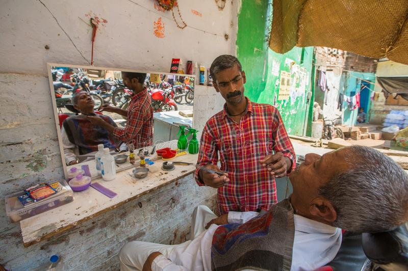 Hairdresser cuts hair of the pilgrim. VARANASI, INDIA - MAR 14, 2018: Hairdresser cuts hair of the pilgrim. A haircut in Varanasi is considered to be a kind of royalty free stock photography