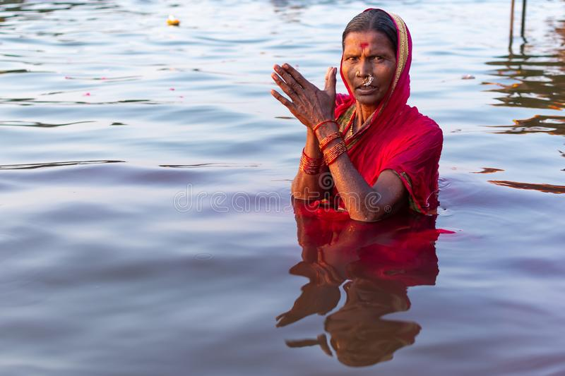 Varanasi, India, 27 Mar 2019 - Hindu woman in sari making offering to the gods in Ganga river at Varanasi, India.  stock photo