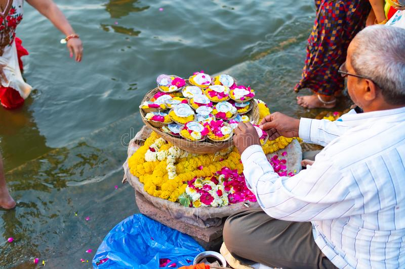 Varanasi, India, 27 Mar 2019 - Indian man selling pooja flowers items for the offering stock photos