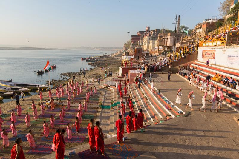 Young hindu monks conduct a ceremony to meet the dawn on banks of Ganges. VARANASI, INDIA - MAR 18, 2018: Young hindu monks conduct a ceremony to meet the dawn royalty free stock images