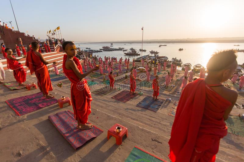 Young hindu monks conduct a ceremony to meet the dawn on banks of Ganges. VARANASI, INDIA - MAR 18, 2018: Young hindu monks conduct a ceremony to meet the dawn stock photography