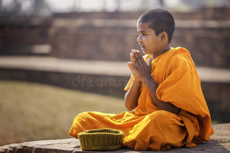 Indian novices are sitting and praying. VARANASI, INDIA – MARCH 24: Nepalese monks are sitting praying at the abode of the Lord Buddha on March 24, 2018 stock image