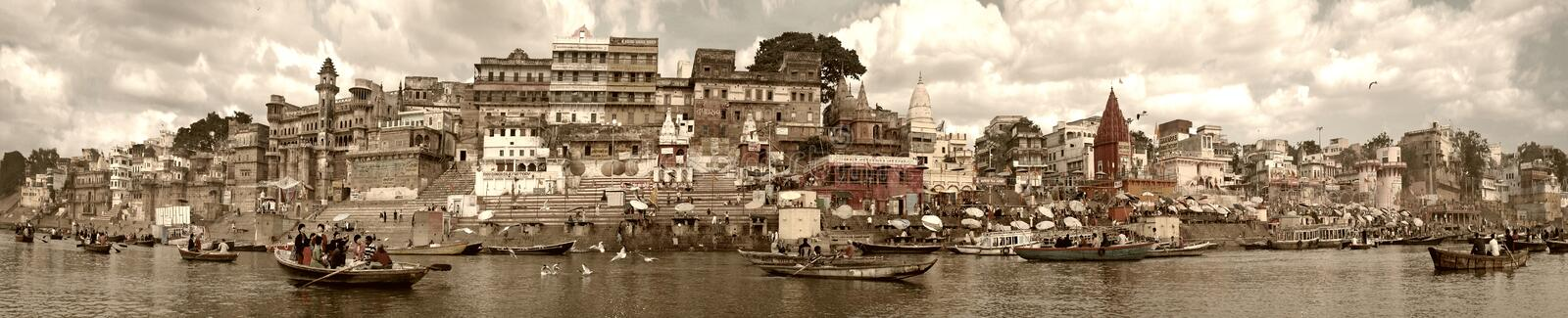 Varanasi, India - November 2009: Boats with tourists and locals floating along the embankment, ghats and ancient buildings. royalty free stock photography