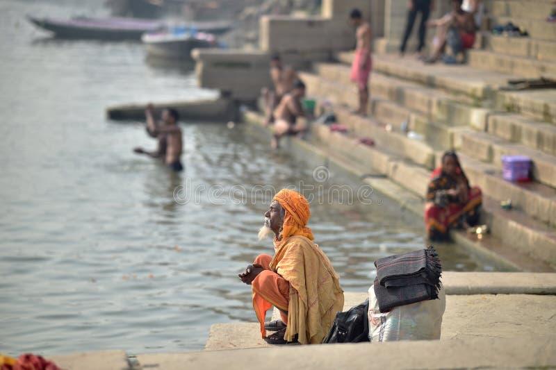 Varanasi, India, 26 November, 2017: Een mens die dichtbij Gange-rivier bidden stock fotografie
