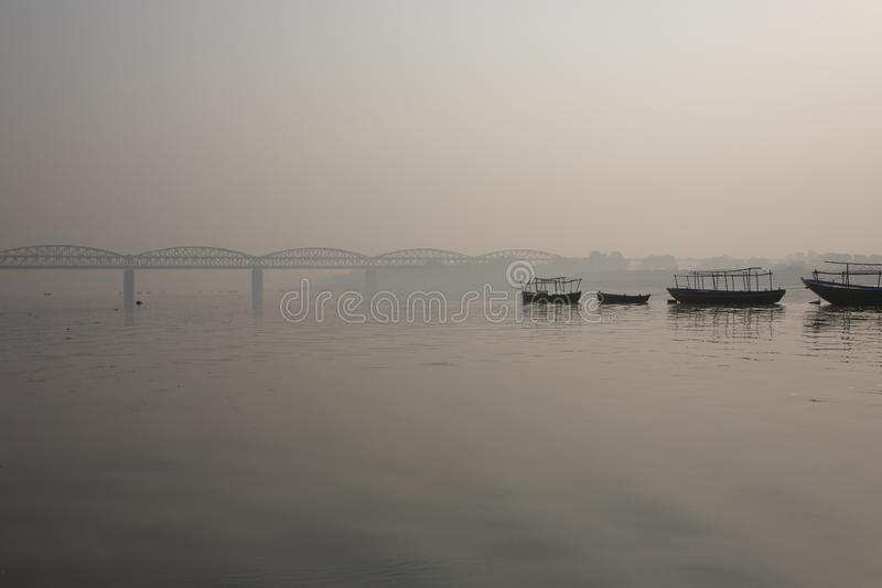 VARANASI, INDIA. View of a Ghat of sacred river Ganges in Varana. Si, India. With Malviya Bridge in the background royalty free stock image