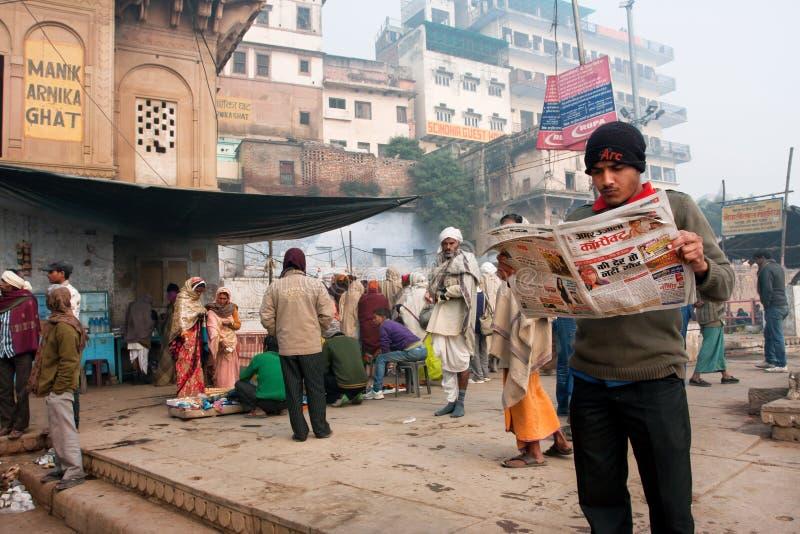 VARANASI, INDIEN: Junger Mann liest eine Zeitung in der Menge von hindischen Leuten am Morgen stockfoto