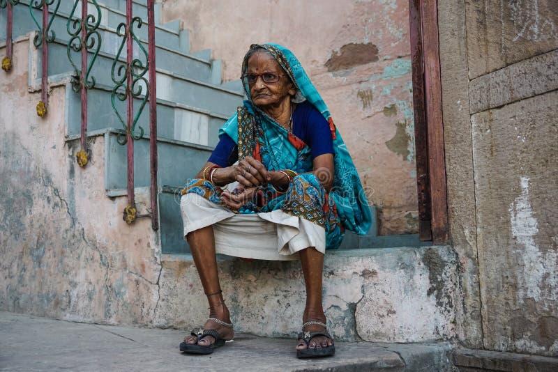 Varanasi, INDIEN - 29. MAI 2017: Alte indische Frau, die auf der Treppe sitzt lizenzfreie stockfotos