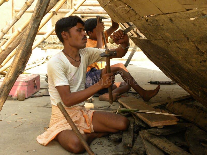 Varanasi, Uttar Pradesh, Índia - 1º de novembro de 2009 carpinteiro que faz barcos de madeira fotografia de stock royalty free