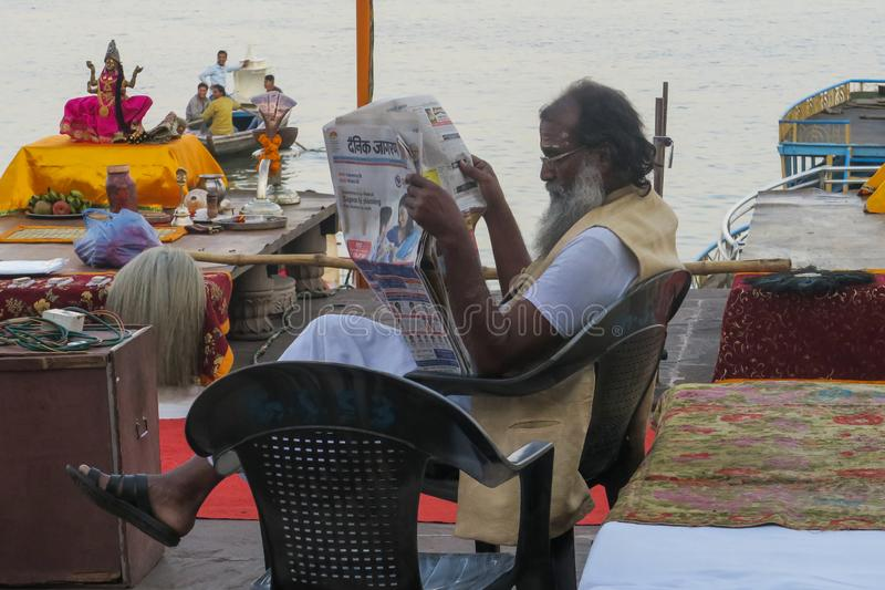 Hindu priest reading newspaper at the border of the river Ganges royalty free stock photos