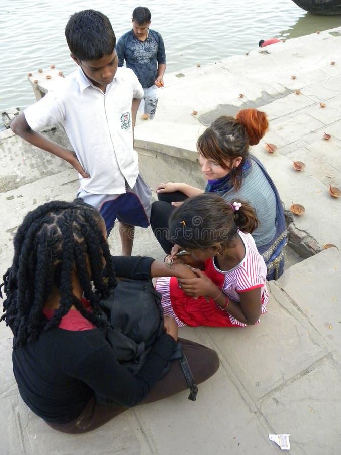 Varanasi, Uttar Pradesh, Indien - 2. November 2009 entwirft junges Mädchen A, das Mehendi macht, auf einem anderen Mädchen, das a stockbilder