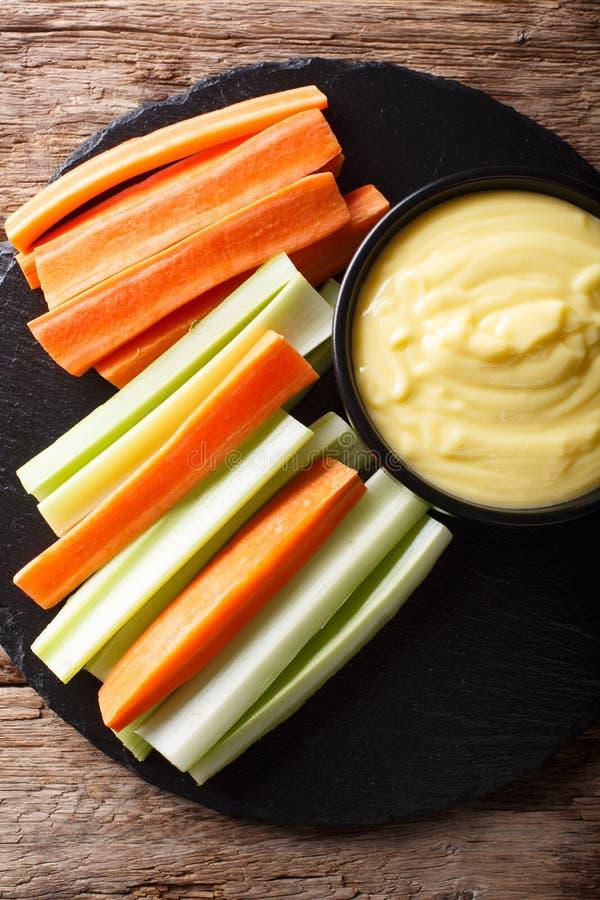 Varas da cenoura e de aipo com mergulho cremoso do queijo em um close-up V foto de stock royalty free