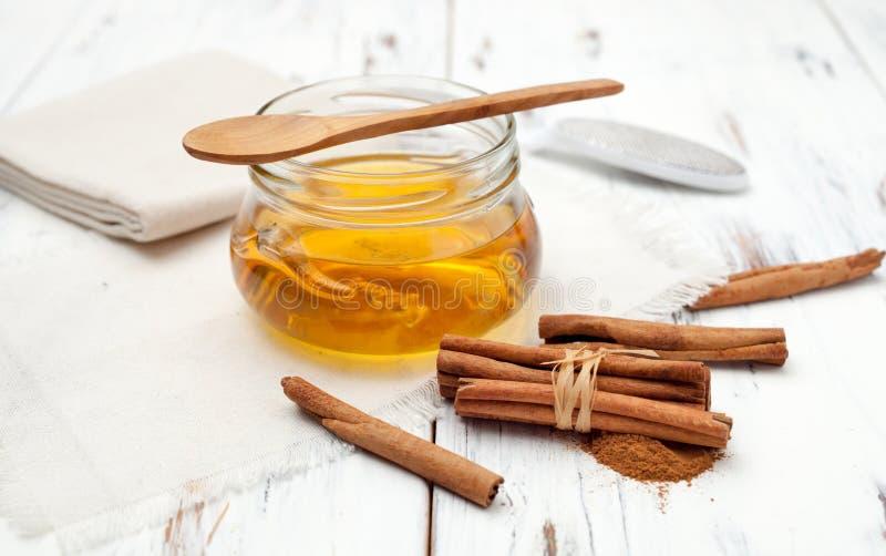 Varas de canela à terra, de mel e de canela no fundo branco imagem de stock royalty free
