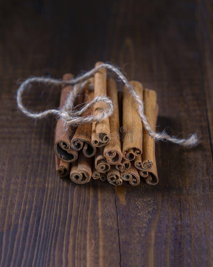 Varas de canela amarradas com corda da juta no fundo de madeira velho no estilo rústico imagem de stock