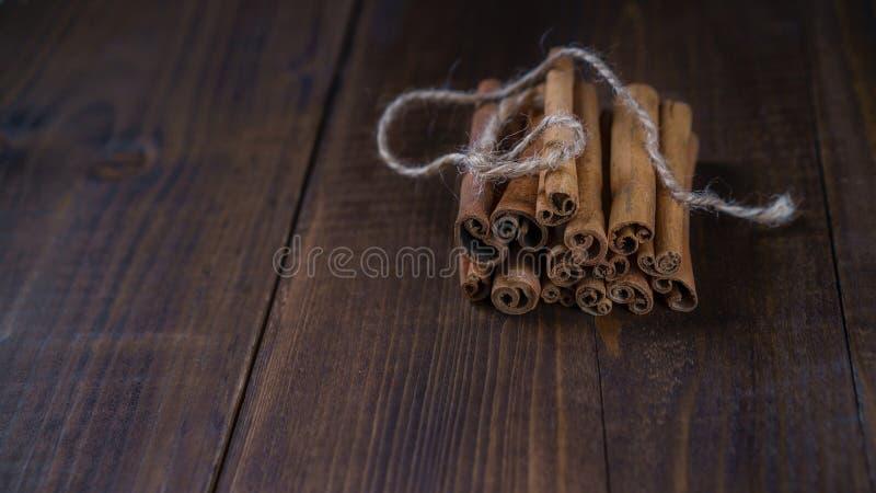 Varas de canela amarradas com corda da juta no fundo de madeira velho no estilo rústico imagem de stock royalty free