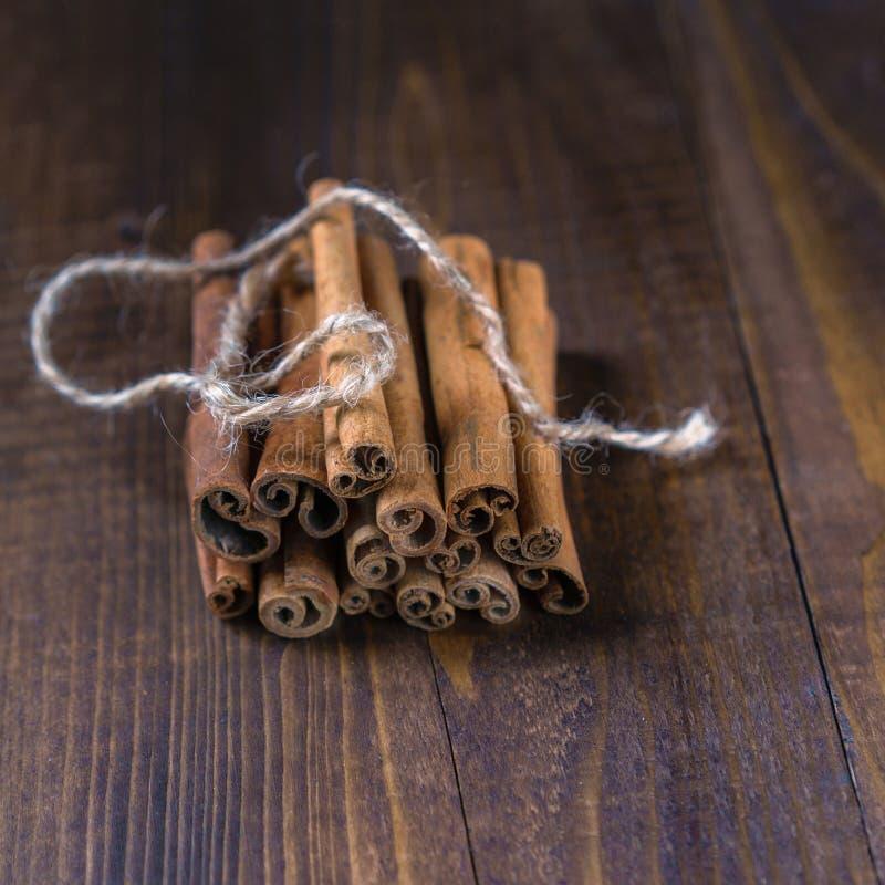 Varas de canela amarradas com corda da juta no fundo de madeira velho no estilo rústico fotos de stock