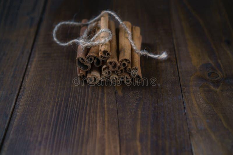 Varas de canela amarradas com corda da juta no fundo de madeira velho no estilo rústico foto de stock
