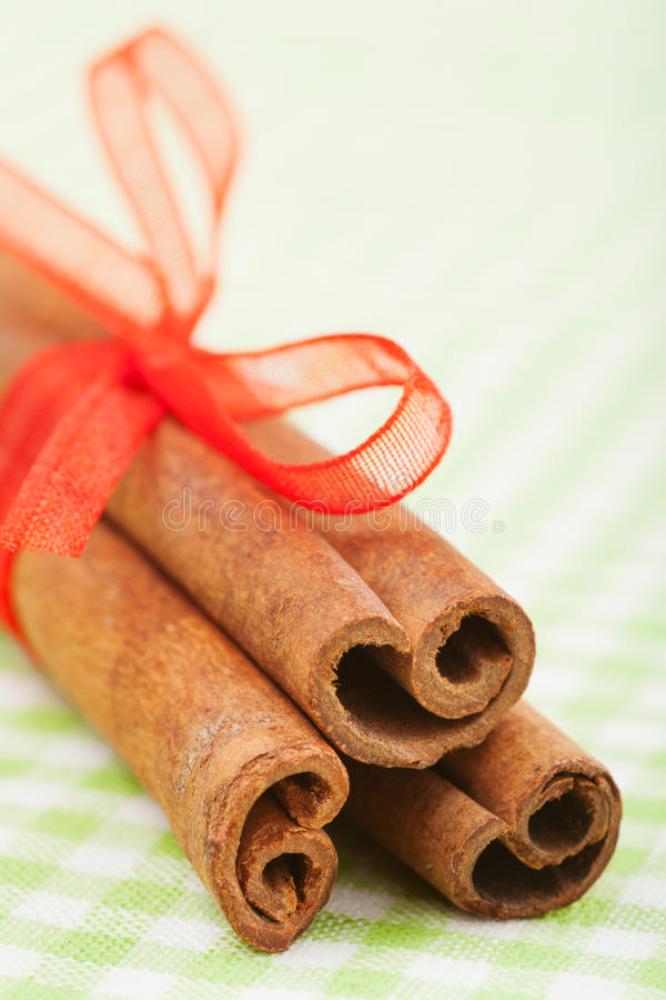 Varas de canela com as varas de canela vermelhas da fita com o close up vermelho da fita foto de stock