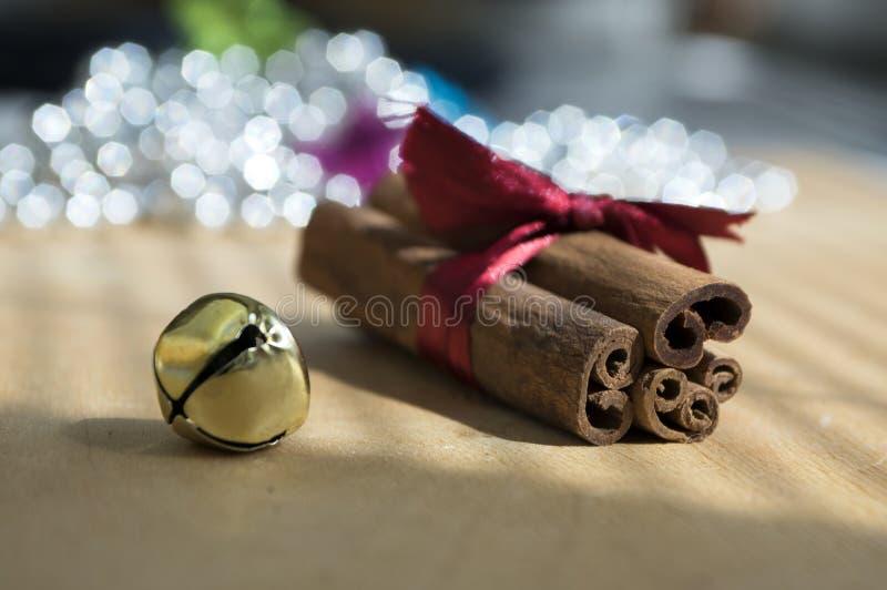 Varas de canela cruas frescas na tabela de madeira amarrada com curva vermelha, sino de tinir, reflexões no fundo imagens de stock