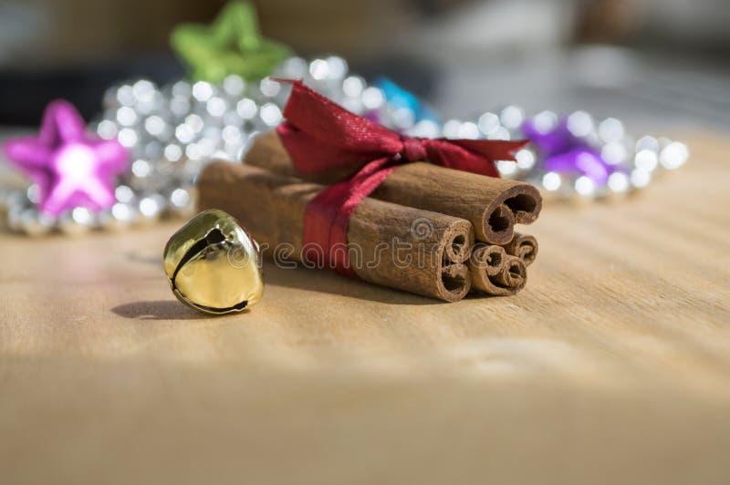 Varas de canela cruas frescas na tabela de madeira amarrada com curva vermelha, sino de tinir, reflexões no fundo foto de stock