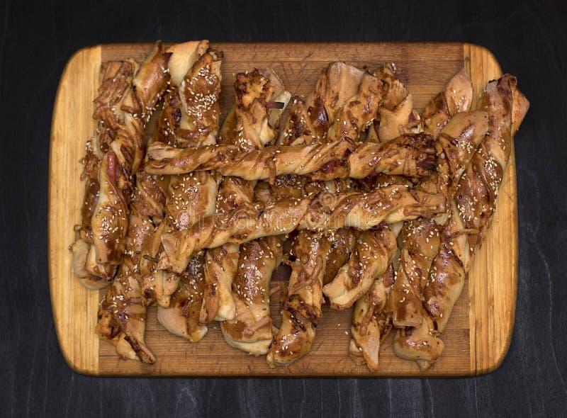 Varas de pão torcidas do queijo com as sementes do presunto e de sésamo em uma placa de madeira foto de stock