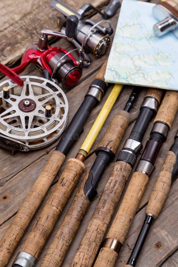 Varas de pesca e carretéis em placas de madeira imagem de stock