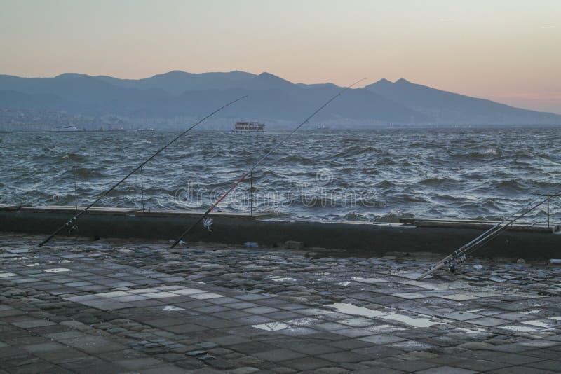 Varas de pesca e opinião do por do sol fotos de stock royalty free