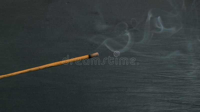 Varas de queimadura do aroma do incenso com fumo no fundo preto imagem de stock