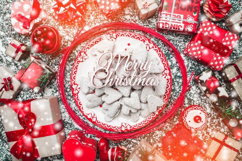 Varas decorativas, con la placa de Navidad y las galletas decorativas, galletas dentro, en gris, piedra, fondo de mármol fotografía de archivo