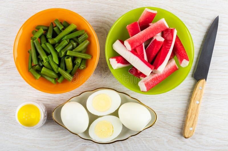 Varas do caranguejo, feijões verdes em umas bacias, sal, ovos cozidos, faca na tabela Vista superior imagem de stock royalty free