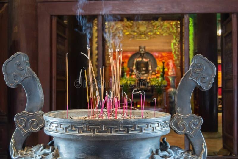 Varas do incenso que queimam-se na escala do frasco da vara de Joss do metal de três pés sobre 400 anos fotos de stock royalty free