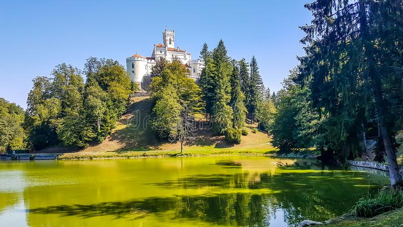 Varazdin - Castle on the hill. A view on Trakoscan castle from the lake side. Castle is located on a small hill and well hidden in between the trees. The lake in stock photo