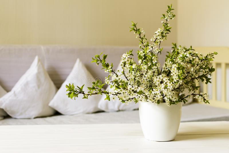 Vardagsrum för landsstil Körsbärsröd blomma i den vita krukan på trätabellen 1 livstid fortfarande arkivfoton