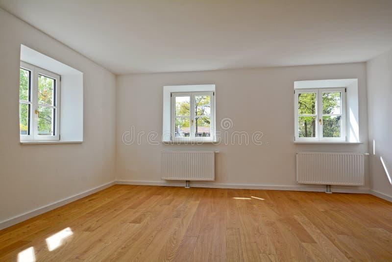 Vardagsrum i en gammal byggnad - lägenhet med träfönster och parkett efter renovering arkivbild
