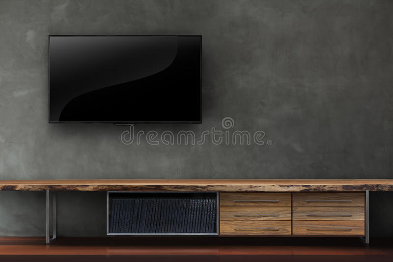 Vardagsrum ledde tv på betongväggen med trätabellmassmediafurn arkivfoto