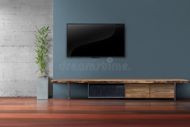 Vardagsrum ledde tv på mörker - blå vägg med trätabellen royaltyfri fotografi