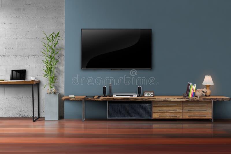 Vardagsrum ledde tv på mörker - blå vägg med trätabellen royaltyfri bild